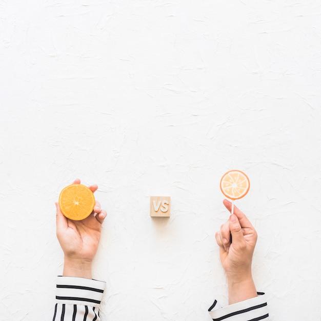 Die hand der geschäftsfrau, die zitrusfruchtscheibe gegen lutscher über weißem hintergrund hält