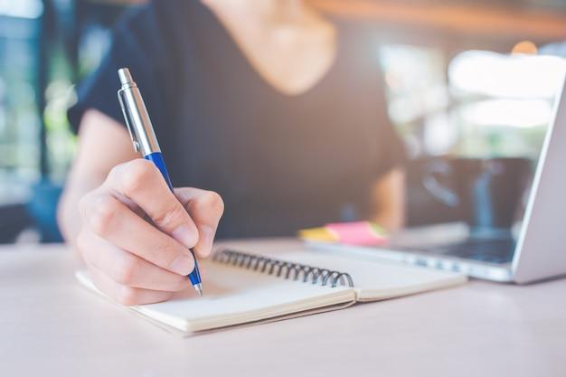 Die hand der geschäftsfrau schreibt auf ein notizbuch mit einem stift.