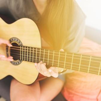 Die hand der jugendlichen, die gitarre spielt