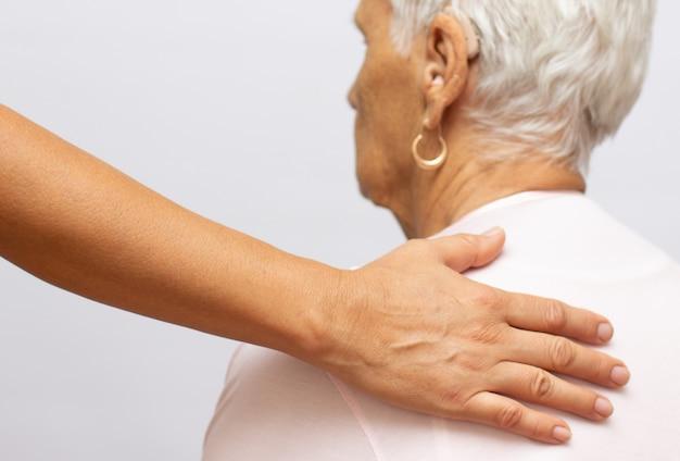 Die hand der jungen eleganten frau auf der schulter der älteren dame. porträt einer lächelnden alten dame mit den händen ihrer krankenschwester auf ihren schultern. zeichen der fürsorge für senioren. helfende hände. pflege für das ältere konzept.