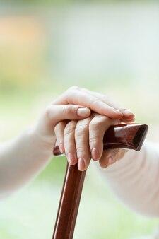 Die hand der jungen pflegekraft wird auf die hand des älteren menschen gelegt, die einen gehstock hält