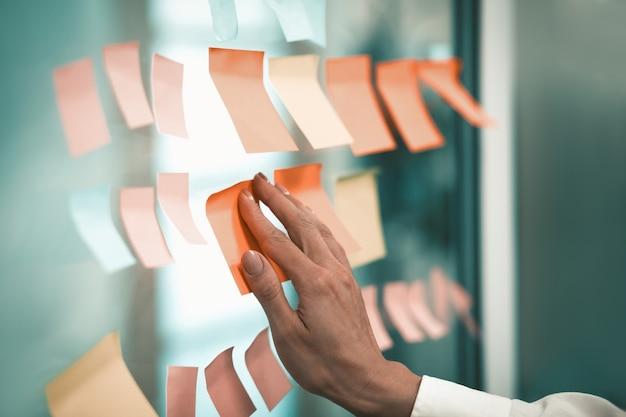 Die hand der kaukasischen frau klebt einen aufkleber auf ein fenster im büro. office notes-konzept.