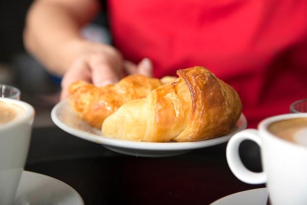 Die hand der kellnerin, die frisches gebackenes hörnchen in der platte anbietet