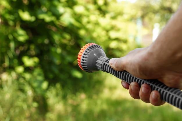Die hand der männer mit gartenbewässerung, das konzept der gartenarbeit