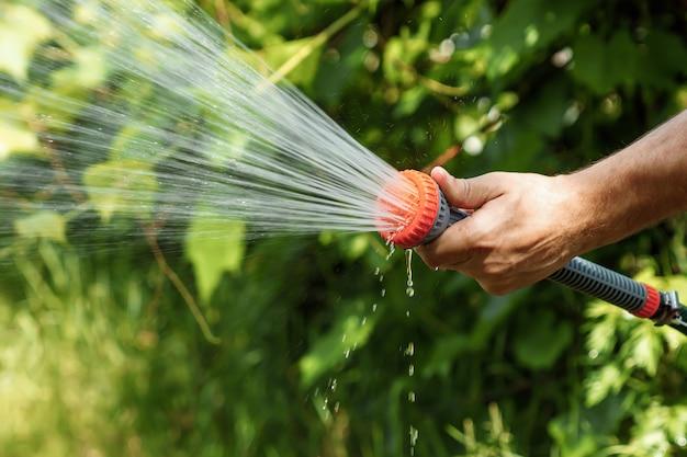 Die hand der männer mit gartenschlauchbewässerungsanlagen