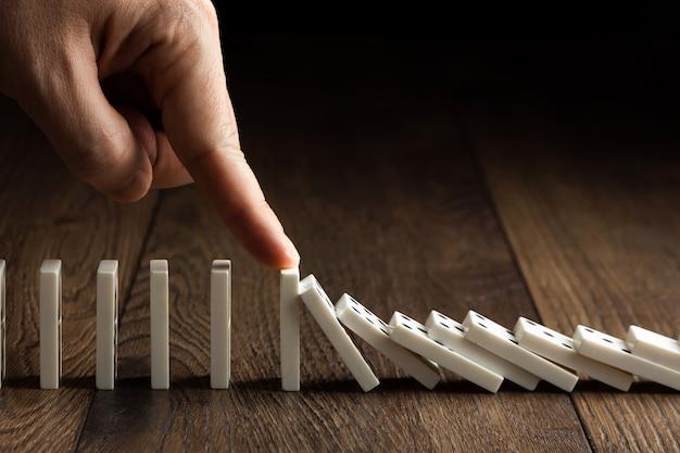 Die hand der männer stoppte dominoeffekt, auf einem braunen holz