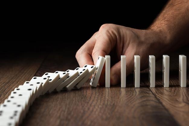 Die hand der männer stoppte dominoeffekt
