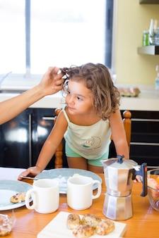 Die hand der mutter, die das haar der tochter während des frühstücks berührt