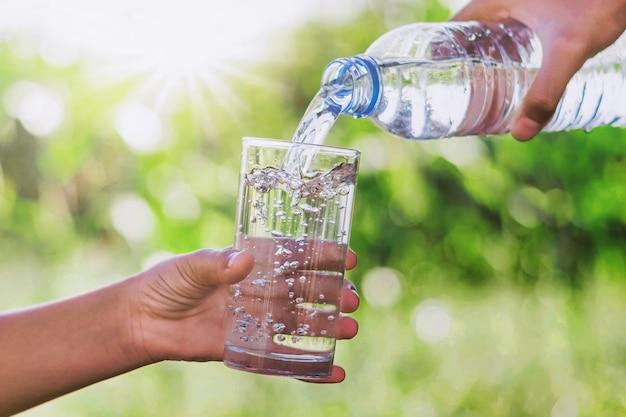 Die hand der mutter, die trinkwasser in glasformflasche gießt, gibt einem kind