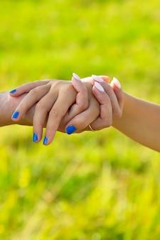 Die hand der mutter führt ihr tochterkind in die sommerwaldnatur im freien, vertraut auf die nähe des familienkonzepts