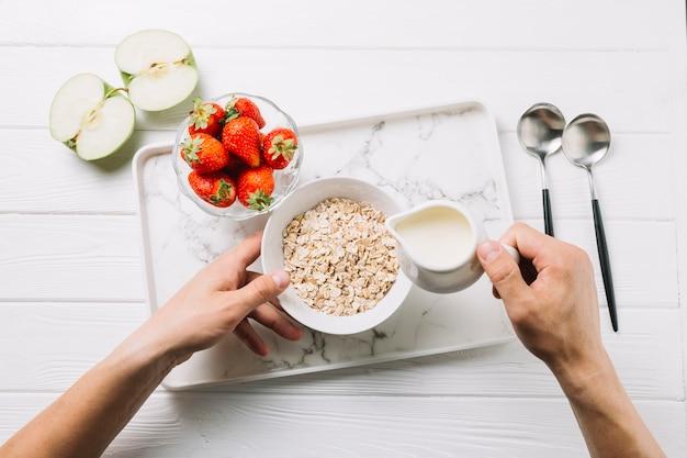 Die hand der person, die milch in der schüssel hafern mit halbiertem grünem apfel und erdbeeren auf tabelle hinzufügt