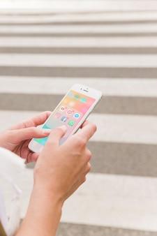 Die Hand der Person, die Mobiltelefon mit Social Media-Mitteilungen auf Schirm hält