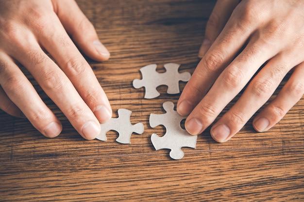 Die hand der person, die weiße puzzleteile auf holzoberfläche verbindet