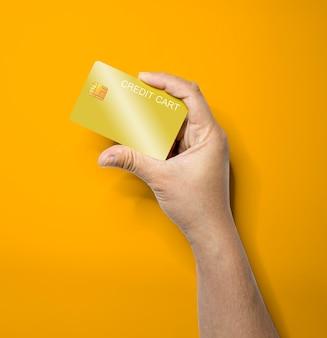 Die hand der person hält mit einer hand eine goldene kreditkarte, eine kreditkarte, mit der waren und dienstleistungen bezahlt werden. isoliert auf einem orangefarbenen hintergrund und beschneidungspfad.