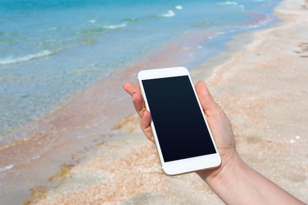 Die hand der schönheit unter verwendung des intelligenten telefons am strand