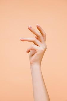 Die hand der sideview-frau auf hellorangefarbenem hintergrund