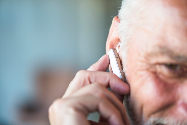 Die hand des älteren mannes, die bluetooth kopfhörer in sein ohr setzt