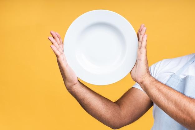 Die hand des afroamerikanischen indischen mannes hält einen weißen leeren teller, der auf gelbem hintergrund isoliert ist.