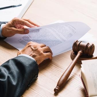 Die hand des anwalts, die dokument mit hammer und holzhammer auf hölzernem schreibtisch hält
