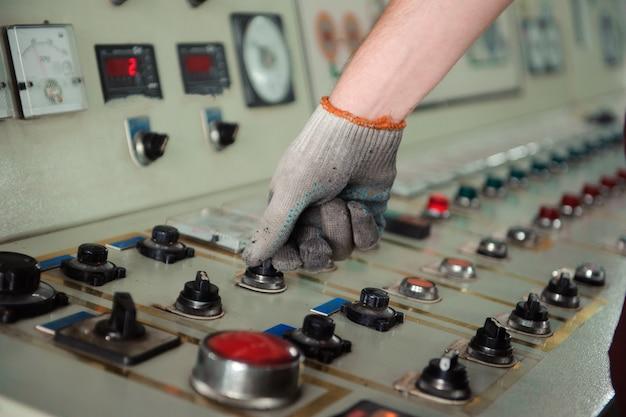 Die hand des arbeiters in einem schmutzigen handschuh in der produktion.
