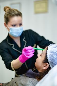 Die hand des arztes im handschuh macht markierungen auf dem gesicht des patienten