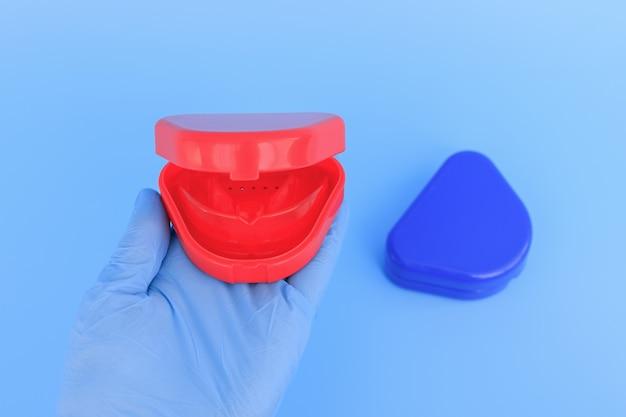 Die hand des arztes in einem blauen handschuh hält einen myofunktionellen trainer zur zahnkorrektur