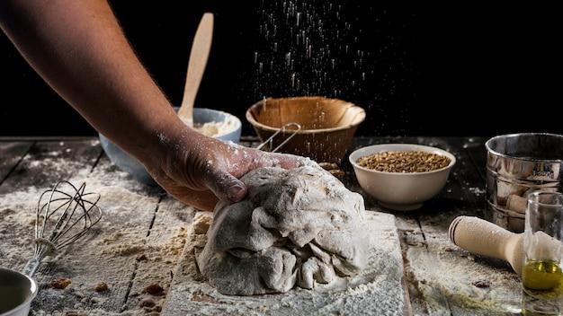 Die hand des bäckers, die den teig auf backentabelle knetet