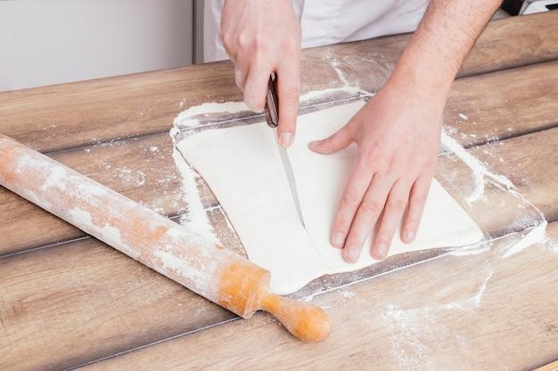 Die hand des bäckers, die den teig mit scharfem messer auf holztisch schneidet