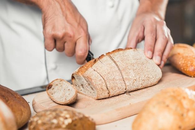 Die hand des bäckers, die frisches brot mit messer schneidet
