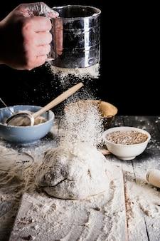 Die hand des bäckers, die mehl mit sieb auf brotteig verschiebt