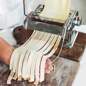 Die hand des bäckers, die rohen teig in bandnudeln auf teigwarenmaschine schneidet