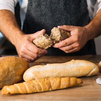 Die hand des bäckers, die vollkornbrot über dem hölzernen schreibtisch bricht