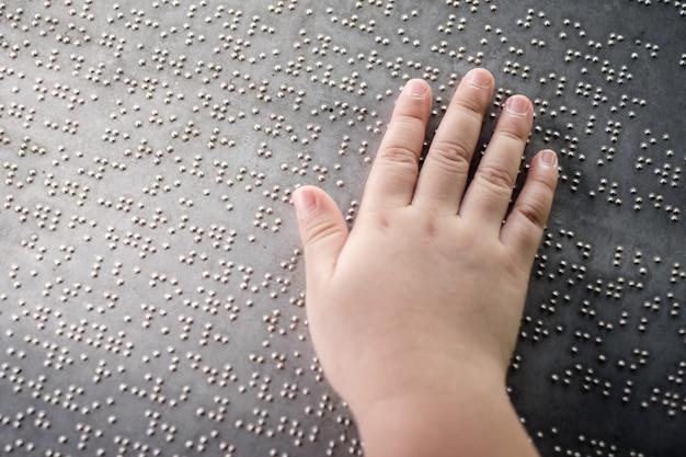 Die hand des blinden kindes, die die braille-buchstaben auf der metallplatte berührt, um es zu verstehen