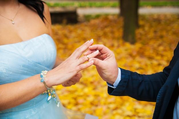 Die hand des bräutigams, die einen ehering auf den finger der braut setzt