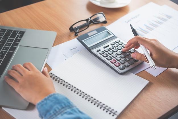 Die hand des buchhalters benutzt den taschenrechner. zur kostenanalyse gewinn- und verlustrechnung und steuerberechnung konzepterstellung von jahresabschlüssen