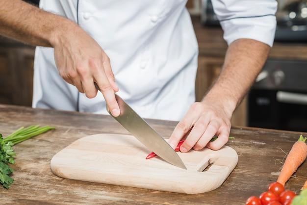 Die hand des chefs, die roten paprika auf hackendem brett schneidet