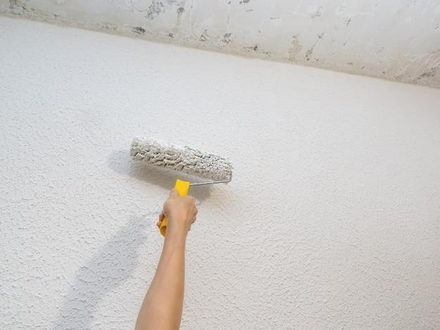 Die hand des dekorateurs, die weiße wand mit rolle malt.