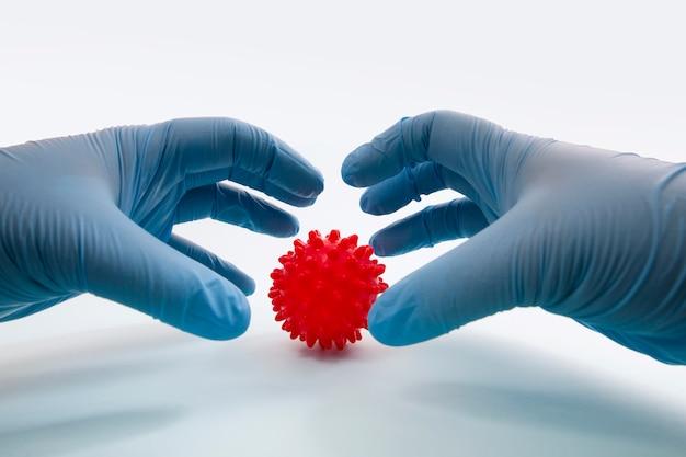 Die hand des doktors hält das konzept des roten virusballs