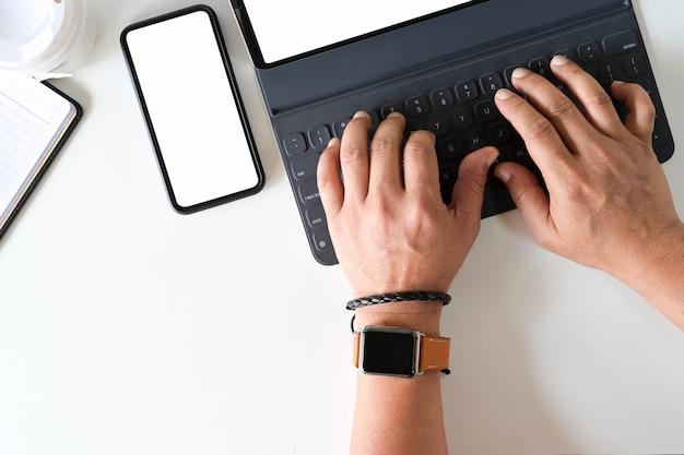 Die hand des draufsichtfreiberuflers unter verwendung auf tastaturtablette auf schreibtischarbeitsplatz.