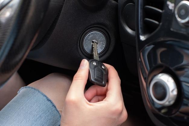 Die hand des fahrers, die einen autoschlüssel einsteckt, schaltet den motor ein und ist bereit für die fahrt.