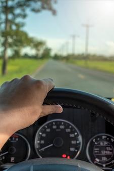 Die hand des fahrers hält das lenkrad im auto. vertikale ansicht reisekonzept