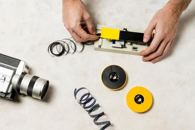 Die hand des fotografen schneidet einen filmstreifen auf konkretem hintergrund