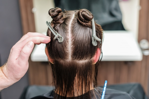 Die hand des friseurs teilt frauenhaar in abschnitte mit clips am friseursalon.