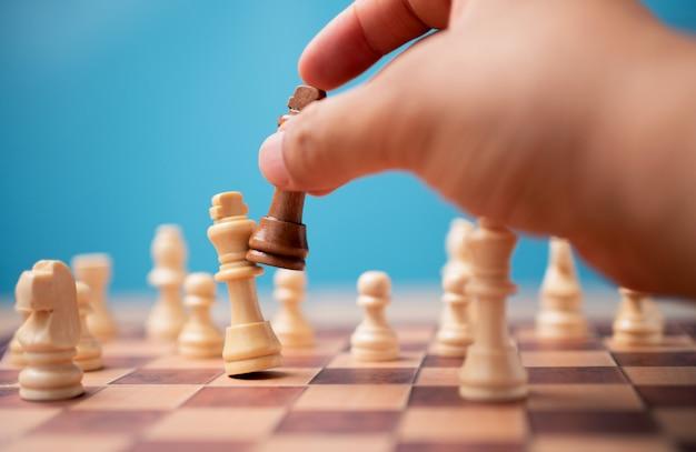 Die hand des geschäftsmannes, der braunes königschach und schachmattkonkurrent hält und die spiele gewinnt.