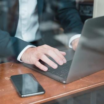 Die hand des geschäftsmannes, die auf laptop über dem schreibtisch schreibt