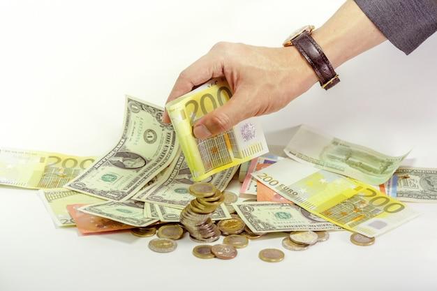 Die hand des geschäftsmannes, die bargeld und münzen des euros 200 hält