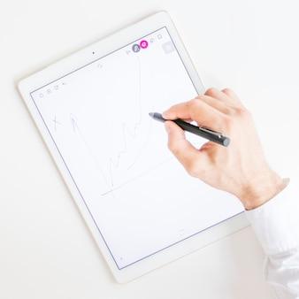 Die hand des geschäftsmannes, die diagramm mit stift auf grafischem digitalem tablettenschirm zeichnet