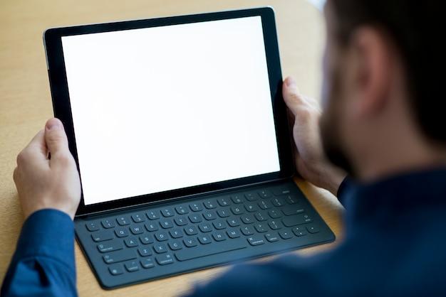 Die hand des geschäftsmannes, die digitale tablette mit leerem weißem schirm hält