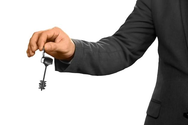 Die hand des geschäftsmannes, die einen schlüssel hält. immobilienmakler auf weißem hintergrund. wählen sie die richtige tür. klopfen und öffnen.