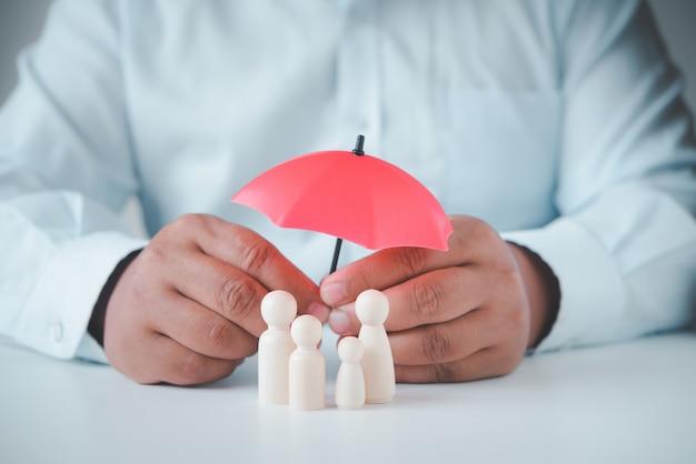 Die hand des geschäftsmannes hält einen regenschirm auf der holzfamilie